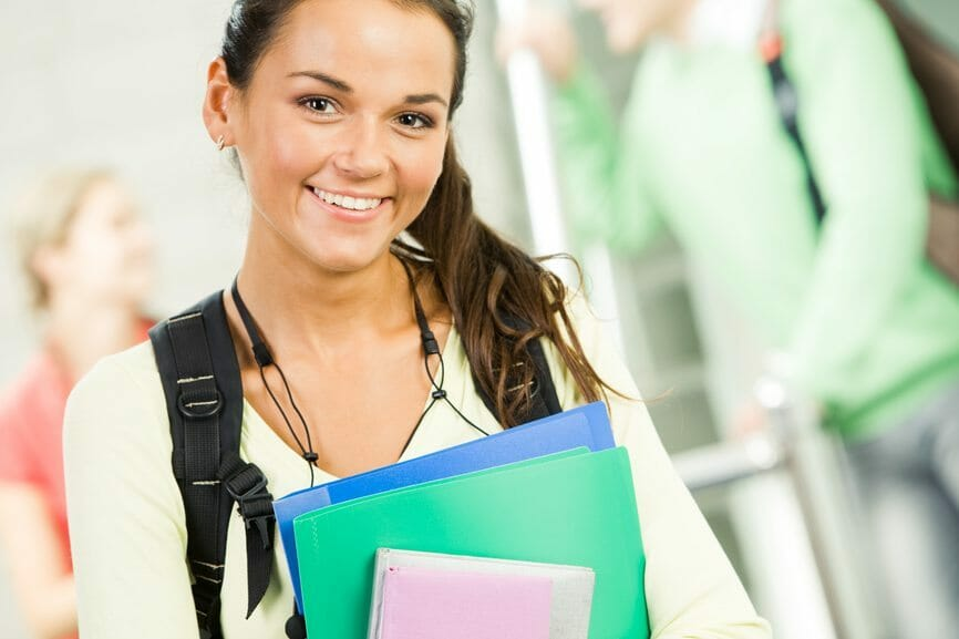 Image of smiling student holding books and looking at camera